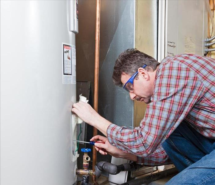 Image of a person performing maintenance on a water heater