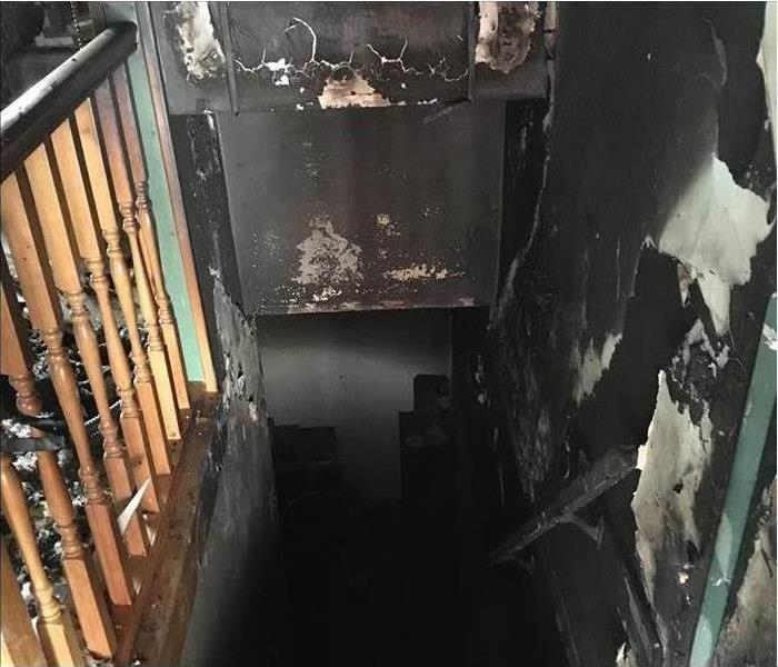 Walls of wooded stairwell damage with smoke and fire damage.