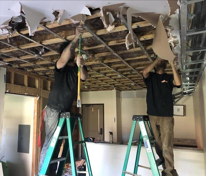 SERVPRO professionals removing ceiling of commercial building due to water damage.